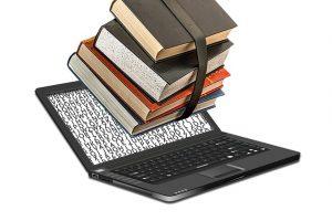 Oppikirjat pinossa tietokoneen päällä